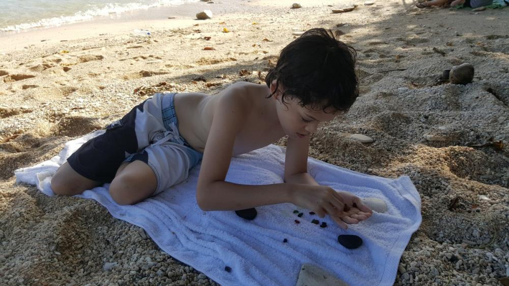12yo making glass rock patterns with worn glass pieces at Flying Fish Cove, Christmas Island