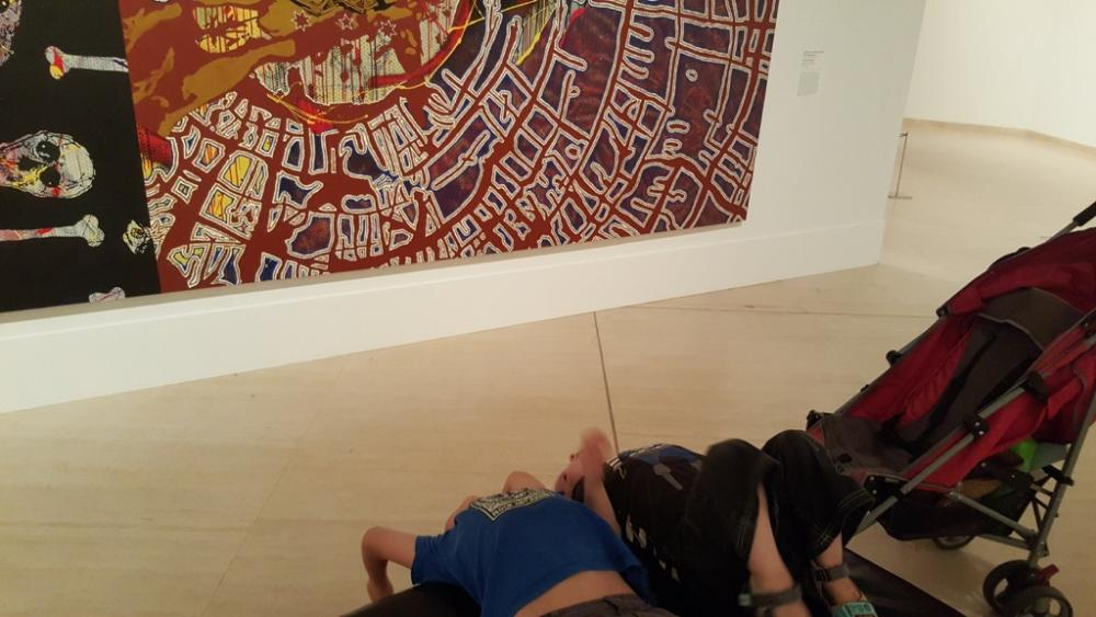 7yo and 3yo trying to understand a picture by getting a different perspective of it (hanging upside down) at Art Gallery of Western Australia
