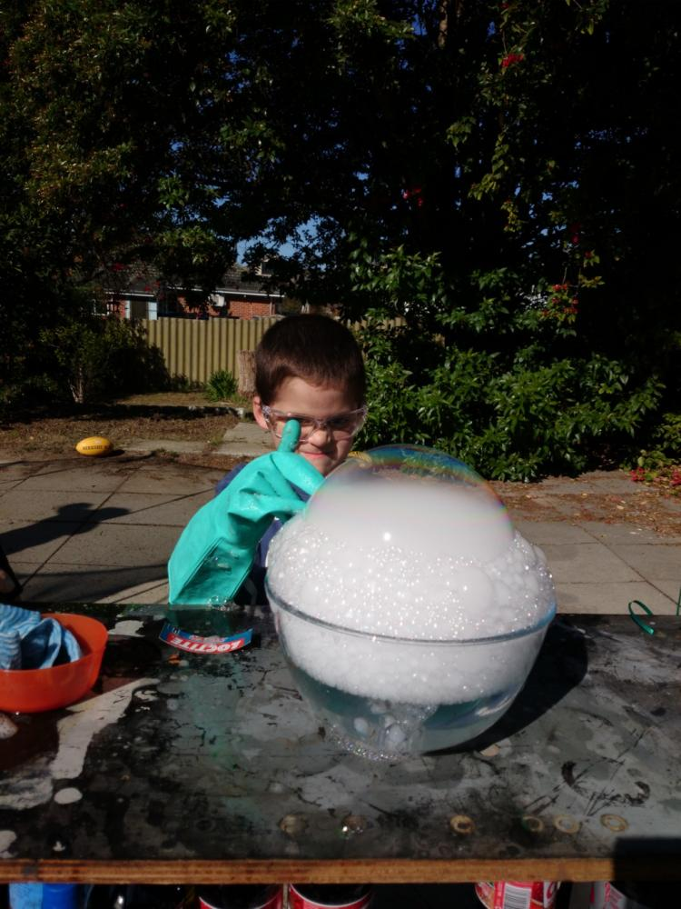 6yo pulling evil scienist face while prepating to pop his giant dry ice bubble
