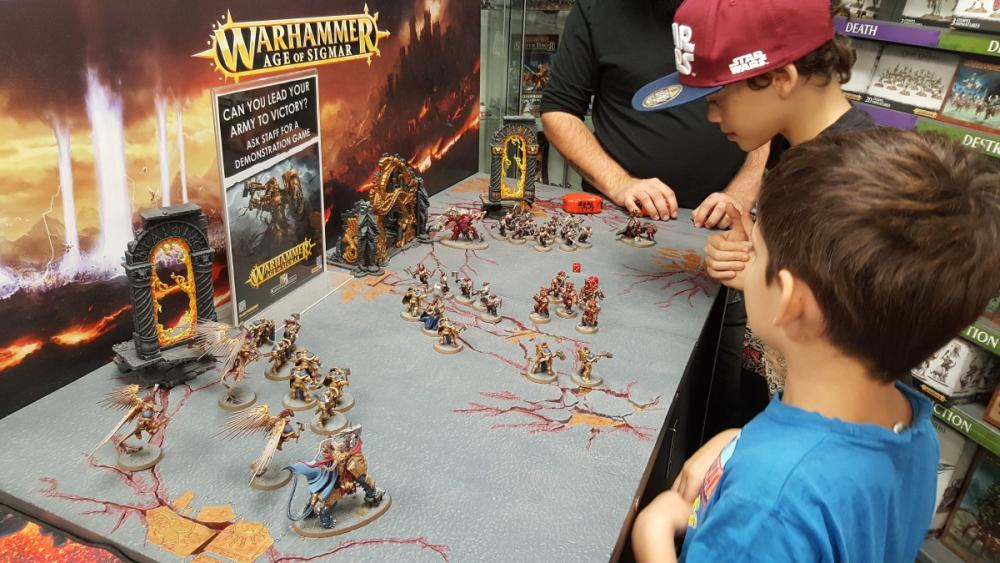 Boys being taught how to play Warhammer Age of Sigma at a Games Workshop in Perth, Western Australia
