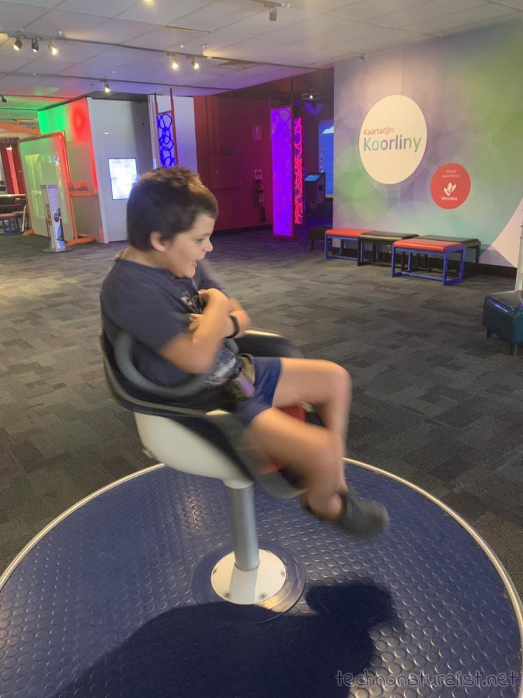 10yo spinning on chair at Scitech, Perth, Western Australia