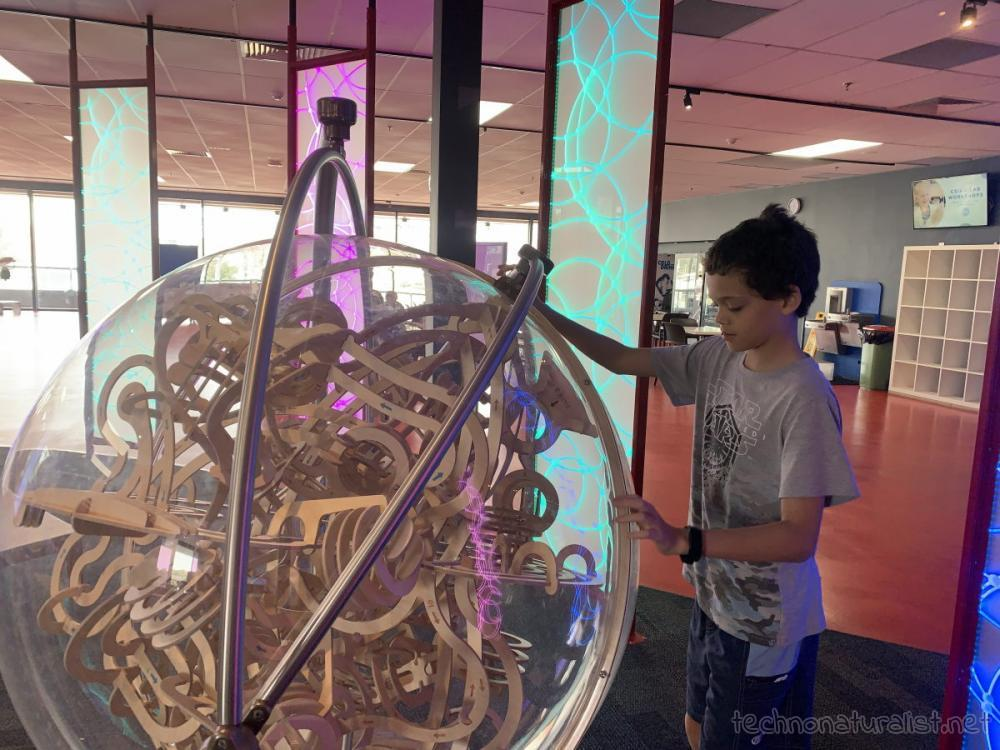 14yo trying to solve giant puzzle ball at Scitech, Perth, Western Australia
